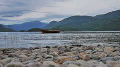 Epic Norwegian landscape, water, shore, mountains, wooden boat Stock Footage