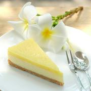 Lemon cheese pie decorated with Frangipani flowers on a white porcelain plate Stock Photos