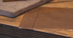 Man's Hands Take The Square Piece of Copper Plate Start to Grind the Edges Stock Footage