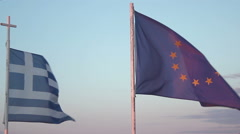 Flags of Greece and EU waving in wind against blue sky background, debt crisis Stock Footage