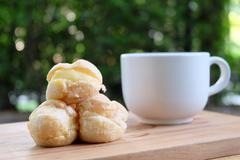 Cream puff with a cup of tea for a relax dessert in the green garden. - stock photo