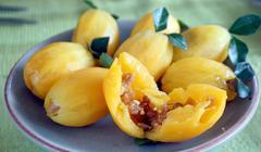 Fusion Thai food, orange plum fruit stuffed with meat - stock photo