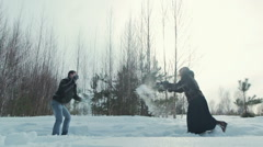 Young couple playing outdoors in the snow, slowmotion Stock Footage