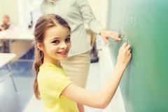little smiling schoolgirl writing on chalk board - stock photo