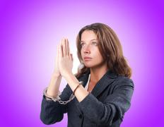 Female businesswoman with handcuffs against gradient Stock Photos