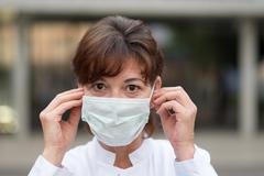 Nurse or doctor wearing a face mask outdoors - stock photo