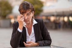 Tearful woman sitting outdoors crying - stock photo