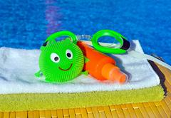 Bath towels, goggles and sun spray, toy against blue water - stock photo