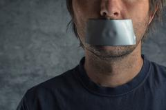 Censorship concept, man with duct tape on mouth Stock Photos