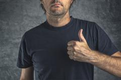 Raised thumb up for approval Stock Photos
