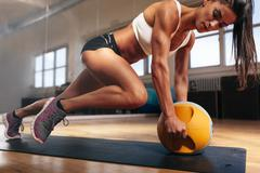 Muscular woman doing intense core workout in gym - stock photo