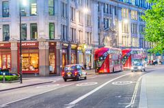 LONDON - JUNE 11, 2015: Tourists and traffic in city streets at night. London Kuvituskuvat
