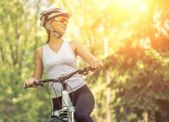 Stock Photo of Portrait of beautiful woman on the bicycle in the park.