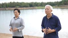 Asian Senior Elderly couple Practice Taichi, Qi Gong exercise next to the lak - stock photo