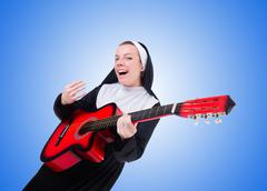Nun playing guitar against the gradient Stock Photos