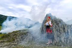 Beautiful blonde woman in old-fashioned dress surrounded by smoke Stock Photos