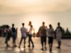 Blurred group of people during sunset - stock photo