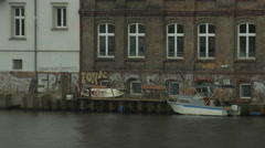 Boat anchored near a brick wall building, on the riverside in Berlin - stock footage