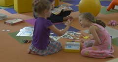 Two Blonde Girls Are Sitting Lying on a Floor Playing Teacher is Reading Stock Footage