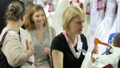 Shop assistant helps shoppers choose the wedding dress Bridal salon. - stock footage