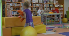 Little Girls are Playing with Toys at the Yellow Mates Boys are Playing at the Stock Footage
