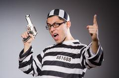 Funny prisoner with firearm isolated on gray Stock Photos