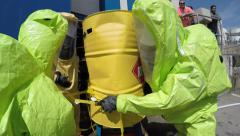 Firefighters seal leak of hazardous corrosive toxic materials from barrels Stock Footage