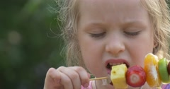 A Little Girl Eating Pieces of Various Fruits on the stick and shows Stock Footage