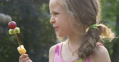 A Little Girl is Eating Pieces of Various Fruits on the stick within her Stock Footage