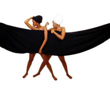 Stock Photo of Two Black Sisters Standing Behind Black Cloth
