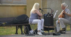 Two Street Musicians - Man and woman - Are Playing Something Gaily on guitars, Stock Footage