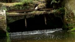 Small weir on the river flows out from cave. Stony, rusty construction of weir. Stock Footage