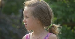 A Little Girl Eating a Cotton Candy using her fingers and turns away Stock Footage