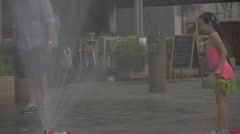 A Teen Girl in Pink T-shirt Bathing in The Spray of water fountain which was Stock Footage