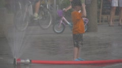 A Fire Hose Splashing a Water on Passers-bye children and adults on a hot Stock Footage
