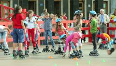Children learn to roller skate on the roll-hall. - stock footage