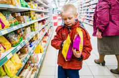 Caucasian boy examining bags of food in grocery store Kuvituskuvat