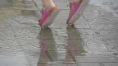 Two Little Girls Cheerfully Jumping Through The Puddles Stock Footage