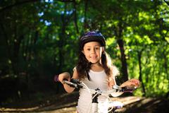 little girl with bicycle in summer park outdoors - stock photo