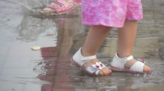 The Girl Dressed in a Bright Purple Dress Goes Through the Puddles. Stock Footage