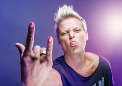 Rocker girl shows rock sign. - stock photo
