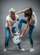 Stock Photo of Two beautiful women playing with clock.
