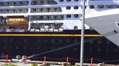 Cruise ship one docked and one passing Stock Footage