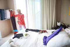Older Caucasian woman choosing outfit in bedroom Stock Photos