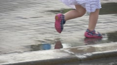 The Little Girl Dressed in a Summer Clothes Play in the Street Stock Footage