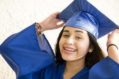 Smiling Hispanic girl wearing graduation robe and mortarboard Stock Photos