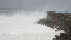 Stormy sea waves crashing against barrier wall during typhoon - stock footage