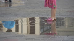 Little Girl in Summer Dress Clothes Plays in Puddle on Crowded Street Stock Footage