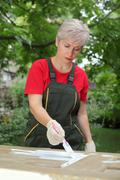 Female worker restoring old wooden door - stock photo