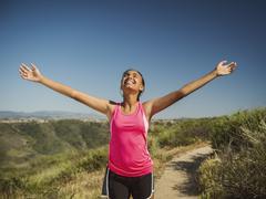 Mixed race girl cheering on hillside path Stock Photos